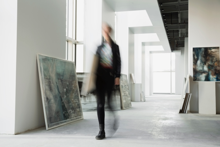 Art dealer walking with paintings in art gallery