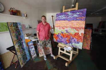 Jeff Ferst in front of his vibrant artworks.