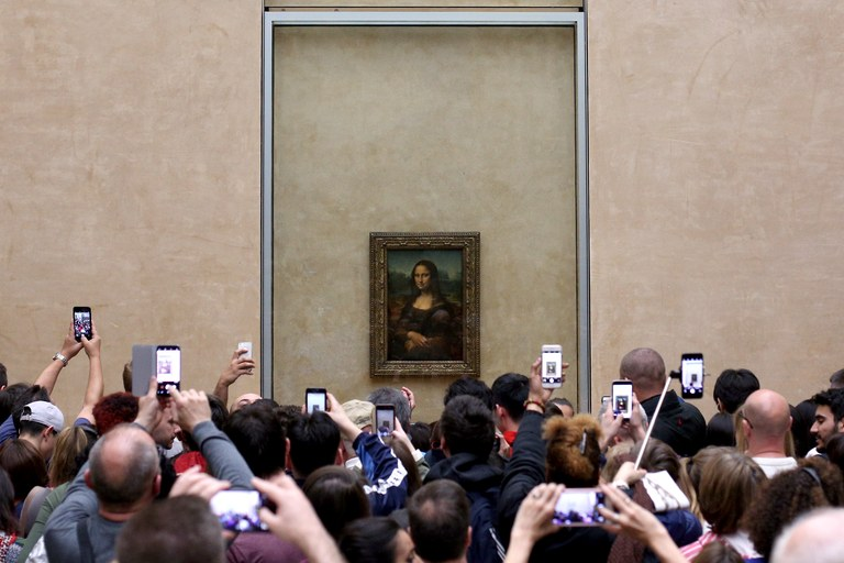 Besucher machen Fotos von Leonardos Mona Lisa. Der Mona-Lisa-Saal ist einer der meistbesuchten Räume des Louvre