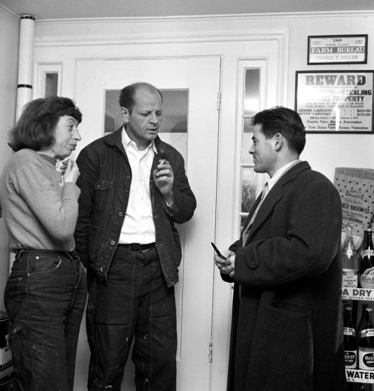 No. 5. At Daniel Miller's general store in Springs, New York, Lee Krasner and Jackson Pollock talk with Tino Navola, late 1940s.