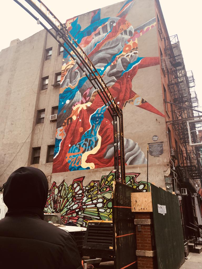 Jason Zanweah à New York devant une fresque de street art